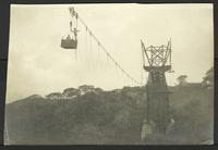 Bridge construction in Costa Rica:  2 men suspended in a high cart