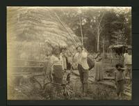 Grass hut with people in front of it