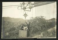 2 men in a hanging cart near land