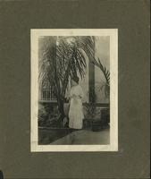 Woman in white dress, holding onto a parasol, looking to her right