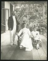 """Man, woman and young girl on porch.  """"Arva 1910"""" written on verso"""
