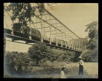 2 men and a lady under the bridge while a train goes over the bridge