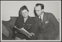 4x7 photo of Peggy and Hobert Skidmore reading a paper during WWII