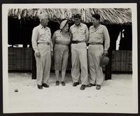3x5 photo of Peggy and three unidentified Army Officers on a Pacific Island in front of thatched structure, WWII