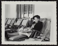 Photo of Peggy having tea on board a ship sitting in a deck chair (2 of 2)