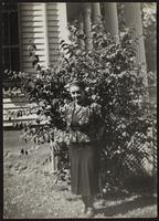Photo of Peggy in front of a house and bush