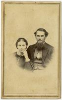 Portrait of a woman with a hairbow resting her hand on her chin and a bearded man with blushed cheeks