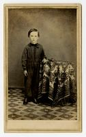 Photo of young boy in dark clothes posing with a decorated table with colored flowers