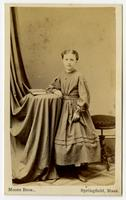Photo of a young girl with dotted dress, book on side table