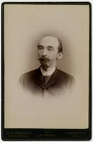 Portrait of a balding man with a mustache and a small beard