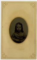 Portrait of little girl with bow on top of her head, framed by mat