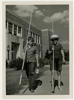 Dick Hunter and Chapin Clark with fishing poles near Pickney School