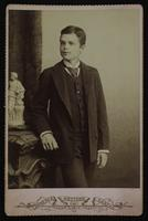 Portrait of a boy with a striped tie posing near a small sculpture