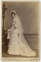 Photo of a standing woman in a wedding dress and long veil