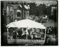 Covered parade float with a cow banner on a desk (Semi-Centennial Parade)