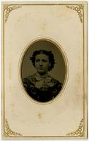 Portrait of a woman with blushed cheeks, gingham dress, and white bow framed by an oval mat