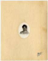 Small portrait of a woman in a floral dress framed by oval mat