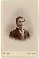 Portrait of a young man with no facial hair and a textured tie