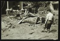 Woman surveying flood damage to house (1951 Flood)