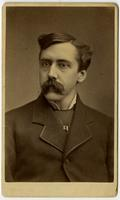 portrait of man with mustache and rectangular metal pendant