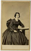 Woman with square-patterned dress posing with table, no tablecloth
