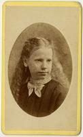Portrait of girl with long wavy hair, earring and white bow on collar
