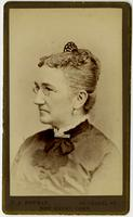 Portrait of old woman with glasses, white earrings, and haircomb