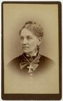Portrait of woman with dangling earrings and large white cross necklace