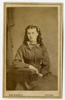 Portrait of a woman with her curled hair down, wearing a choker and a bow
