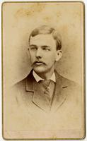 Portrait of a young man with a mustache and textured jacket