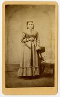 Photo a standing woman with pulled back curls and a choker. Posing with tassled chair