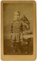 Photo of an infant standing with an ornate chair