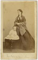 Photo of a standing woman with a gingham shawl posing with an infant on a chair