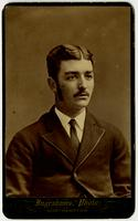 Portrait of a man with a mustache, sideburns, tie, and textured jacket