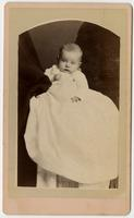 Portrait of a baby in a long white dress
