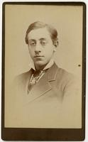 Portrait of a young man with a dark tie with white crisscrossing lines