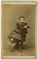 Portrait of a child in a dark plaid dress posing on a stuffed tassled chair