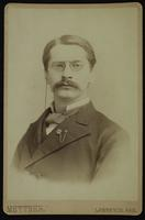 Portrait of a man with a mustache and a chain on his glasses