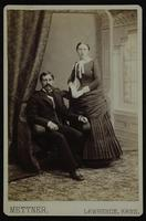 Photo of a sitting man and a standing woman