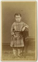 Portrait of a young boy in a plaid dress with pockets and striped leggings