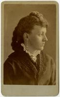Profile portrait of a woman with dangling earrings and tied back, braided hair