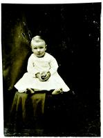 Photo of an infant with blushed cheeks in a white dress