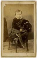 Portrait of an infant with long boots on a tassled chair