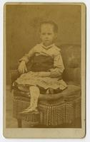 Portrait of a child on a stuffed tassled chair