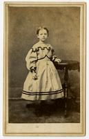 Photo of a a young girl in a white dress with black trim