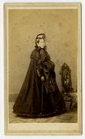 Photo of a woman with a bonnet, fur muff, and decorative chair