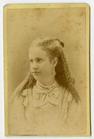 Portrait of a woman with long curly hair, dnagling earrings, and a white bow on her collar
