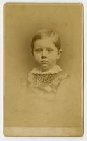 Small portrait of an infant with a white frilled collar and curvy black design