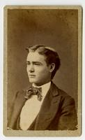 Portrait of a young man without facial hair wearing a striped bowtie