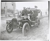 """Family in Reo Auto with Trophy on Hood (titled """"the Winner of The Lyric Trophy - Lyric Cup Run Nov. 9 and 10 1908"""")"""
